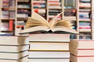 aufgeschlagener Roman auf Bücherstapel